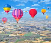 Flight of hot air balloons above the countryside. — Stock Photo