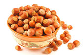 Closeup view of hazelnuts in a bowl on white background. — Stock Photo