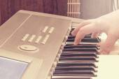 Male hand on the keyboard and guitar. — Stock Photo