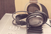 Digital midi keyboard, headphones and acoustic guitar. — Stock Photo
