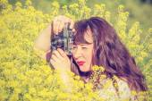Woman shooting flowers on the meadow. — Stock Photo
