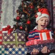 Happy boy with christmas present boxes — Stock Photo #59023355