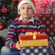Happy boy with christmas present boxes — Stock Photo #59023395