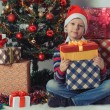 Happy boy with christmas present boxes — Stock Photo #59023401