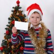 Boy holding greeting card. Christmastime — Stock Photo #59023531