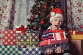 Happy boy with christmas present boxes — Stockfoto