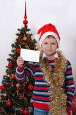 Boy holding greeting card. Christmastime — Stock Photo