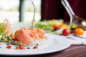 Creative composition delicious fresh smoked sliced salmon with tartar sauce on a white plate on a wooden table in a restaurant with decor — Stock Photo