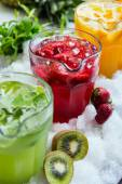 A mix of several bright colored delicious cold lemonade carafes of kiwi and orange and strawberry on the table with creative composition of ice berries oranges and mint. soft focus — Stock Photo