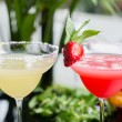 A mix of the two bright refreshing cocktails: lime daiquiri and strawberry daiquiri on a table in a restaurant with creative decoration of salt on the edge of the glass with fresh mint and lime slices — Stock Photo #73602571