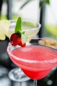 A mix of the two bright refreshing cocktails: lime daiquiri and strawberry daiquiri on a table in a restaurant with creative decoration of salt on the edge of the glass with fresh mint and lime slices — Stock Photo