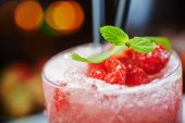 Bright beautiful and tasty alcoholic cocktail or lemonade with a cap of frozen ice, mint and fresh raspberries on the bar with a nice bokeh of the disco light. soft focus. — Stock Photo