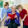 Grandmother Reading Book to Grand Children. — Stock Photo #61182581