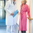 Doctor talking to an elderly woman in the corridor. — Stock Photo #61182715