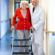 Physician helping a senior woman in a walker. — Stock Photo #61182733
