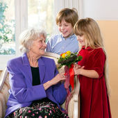 Children giving grandmother flowers. — Fotografia Stock