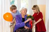 Grandma receives flowers from grand kids. — ストック写真