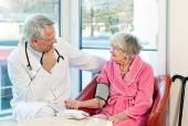 Doctor taking an elderly womans blood pressure. — Stock Photo