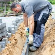 Worker puts stone slabs — Stock Photo #62672111