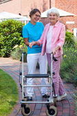 Care assistant helping elderly lady — Stock Photo