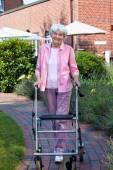 Elderly lady using walker — Stock Photo