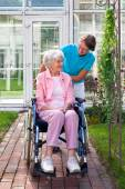 Elderly lady in wheelchair with care assistant — Stock Photo