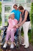 Care Takers and Patient on Wheel Chair — Stock Photo