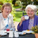 Senior Women Relaxing at Garden Table — Stock Photo #68905867
