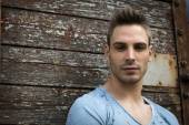 Young man portrait against old wood wall — Stock Photo