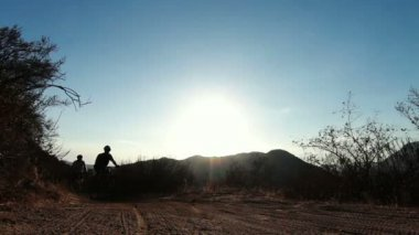 Silhouette Two People Mountain Biking At Sunset Outside — Stock Video