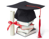 Graduation cap and diploma with books — Stock Photo