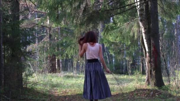 девушка в юбке гуляет по лесу