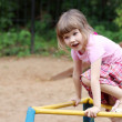 Beautiful cute little girl plays at playground on warm sunny day — Stock Photo #60123503