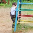 Cute handsome little boy in brown suit climbs up on playground — Stock Photo #60123509