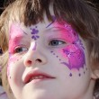 Happy little girl with pictured purple butterfly on face with ti — Stock Photo #60124733
