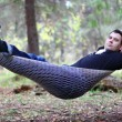 Handsome young man lies in hammock in woods at dull autumn day — Stock Photo #60125671