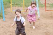 Little Boy in overalls runs away from girl on warm sunny day — Stock Photo