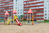 Colorful playground in sand next to high-rise residential buildi — Stock Photo