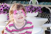 Happy little girl with pictured purple butterfly on face near po — Stock Photo