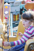Beautiful little girl rides on carousel pirate ship in summer pa — Stock Photo