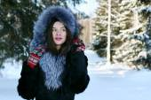 Beautiful girl in fur coat dreams and looks away in winter fores — Stock Photo