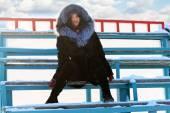 Beautiful girl in black fur coat sits on wooden old bleachers in — Стоковое фото
