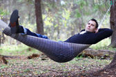 Handsome young man lies in hammock in woods at dull autumn day — Stock Photo