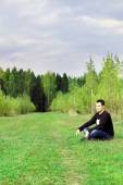 Man sits on grass on edge of forest at autumn dull day and think — Stock Photo