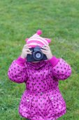 Little girl in pink photographs by camera rarity outdoors at aut — Stock Photo