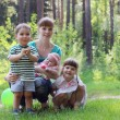 Happy young mother with three smiling kids in summer sunny fores — Stock Photo #70084567