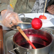 Male hand turns red sweet apple on stick in syrup outdoor at sun — Stock Photo #70084683