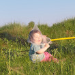 Laughing cute little boy sitting on grass caught butterfly net — Stock Photo #70084865