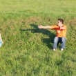 Little cute girl runs next to his father on grass on summer day — Stock Photo #70084937