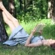 Beautiful girl in dress lying under tree on grass and reading bo — Stock Photo #70085323